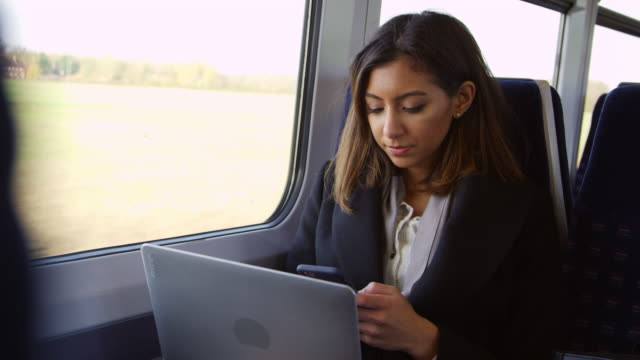 vídeos de stock e filmes b-roll de businesswoman using laptop and phone on train shot on r3d - cultura indiana