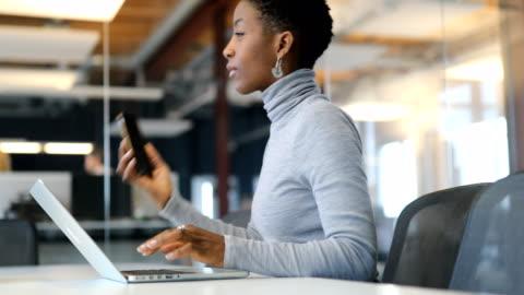 dizüstü bilgisayar ve akıllı telefon kullanarak iş kadını - dişiler stok videoları ve detay görüntü çekimi