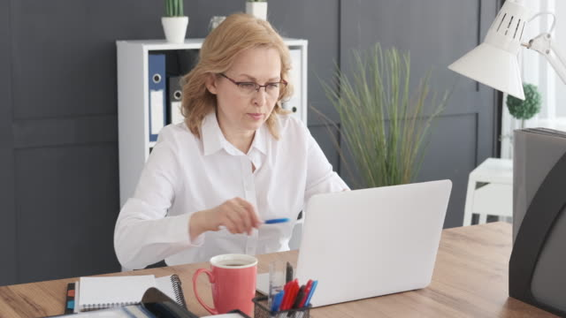 Businesswoman using laptop and taking notes at office