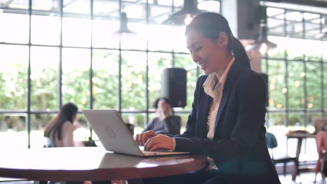 businesswoman using laptop in cafe - fare una prenotazione video stock e b–roll