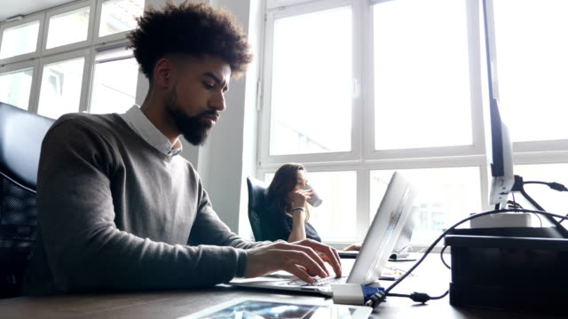 Businesswoman using laptop with colleague at desk