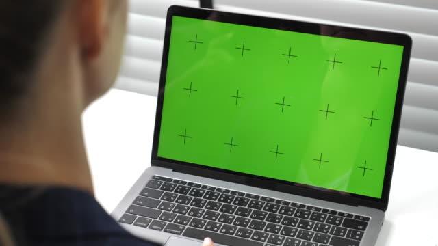 affärskvinna använder laptop med grön skärm på sitt kontor - skrollning bildbanksvideor och videomaterial från bakom kulisserna