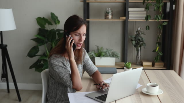 Businesswoman using laptop writing notes talk on phone to client