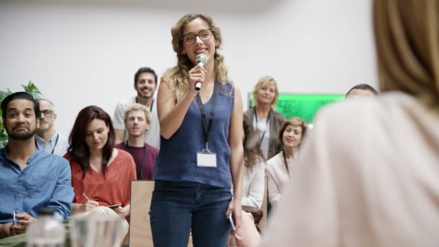 Businesswoman using microphone at networking event Businesswoman talking into microphone at networking event. Audience is listening to female professional in meeting. They are attending business event. event stock videos & royalty-free footage