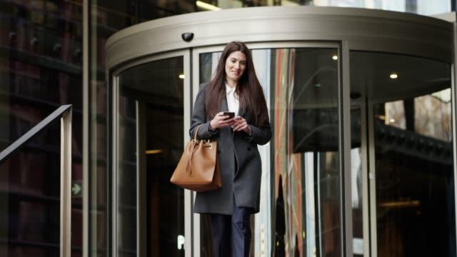 businesswoman using mobile phone after work - odejście filmów i materiałów b-roll