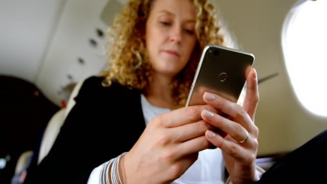 geschäftsfrau mit handy im privat-jet 4k - gefreiter stock-videos und b-roll-filmmaterial