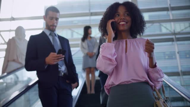 在現代辦公室 4k 的自動扶梯上使用手機的女商人 - 三四十歲的人 個影片檔及 b 捲影像