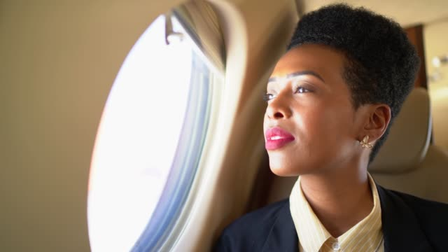 stockvideo's en b-roll-footage met zakenvrouw die telefoon gebruikt en door corporate jet window kijkt - woman very rich