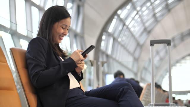 affärskvinna med telefon på flygplats - affärsresa bildbanksvideor och videomaterial från bakom kulisserna