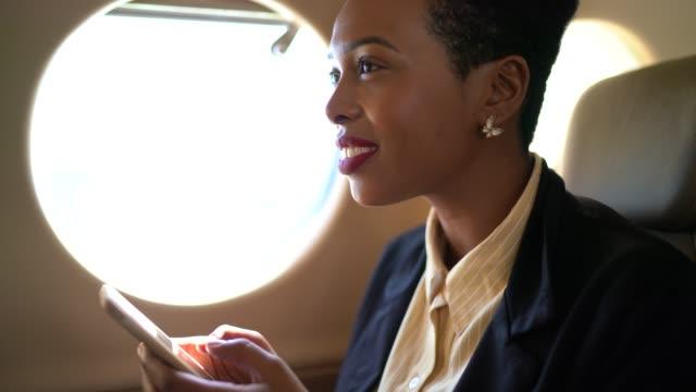 affärskvinna använder telefonen i en corporate jet - affärsresa bildbanksvideor och videomaterial från bakom kulisserna
