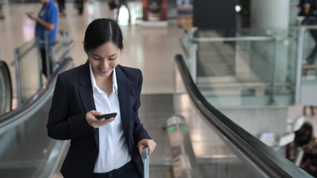 businesswoman using phone on escalator at airport - escalator video stock e b–roll