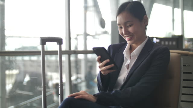 Businesswoman using Smart phone at airport, Business travel
