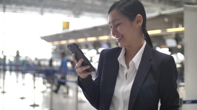 stockvideo's en b-roll-footage met zakenvrouw met behulp van smart phone op luchthaven - zakenreis