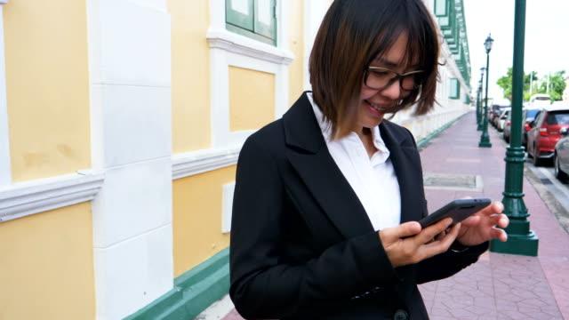stockvideo's en b-roll-footage met zakenvrouw met behulp van slimme telefoon in bangkok - men blazer