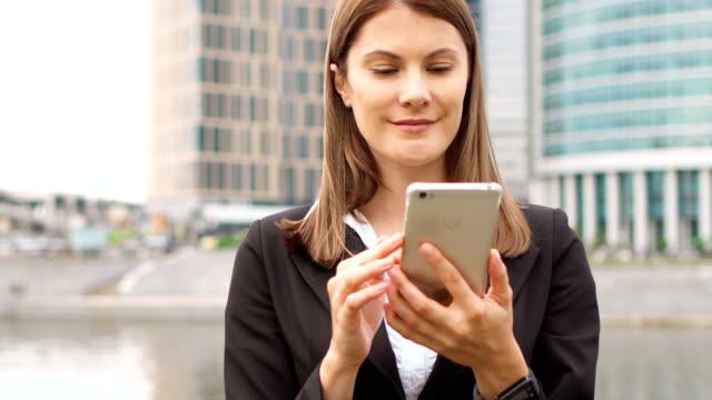 geschäftsfrau mit smartphone in innenstadt, professionelle weibliche surfen im chat lesen von nachrichten - formelle geschäftskleidung stock-videos und b-roll-filmmaterial
