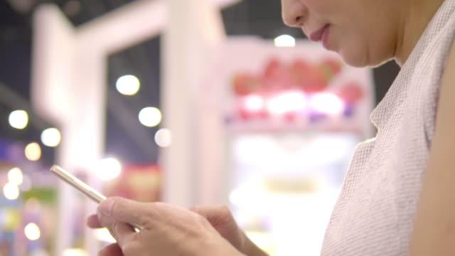 スマートフォンを利用したビジネスウーマン - 展示会点の映像素材/bロール