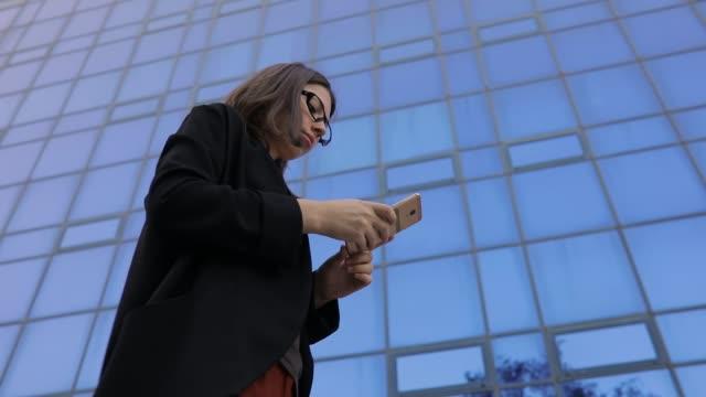 geschäftsfrau mit smartphone gegen hohe bürogebäude, ansicht von unten - weibliche führungskraft stock-videos und b-roll-filmmaterial