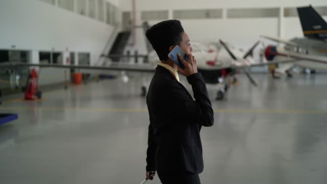 Businesswoman using smartphone in a hangar