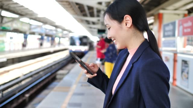 Businesswoman using Smartphone on Subway Station