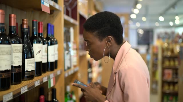 Businesswoman using smartphone while shopping in a supermarket