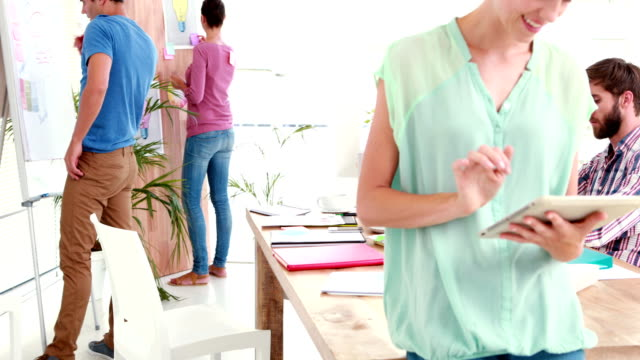 Businesswoman using tablet in the office with colleagues behind Businesswoman using tablet in the office with colleagues behind in the office employee engagement stock videos & royalty-free footage