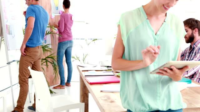 vídeos de stock e filmes b-roll de mulher de negócios com tablet no escritório com colegas por trás - envolvimento dos funcionários