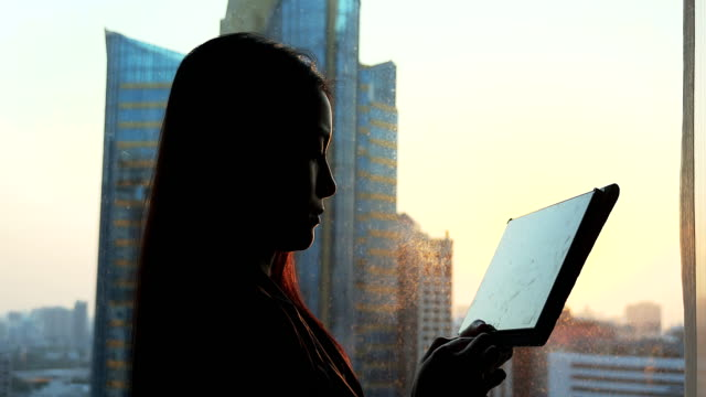 Businesswoman using tablet near the window at sunset period. video