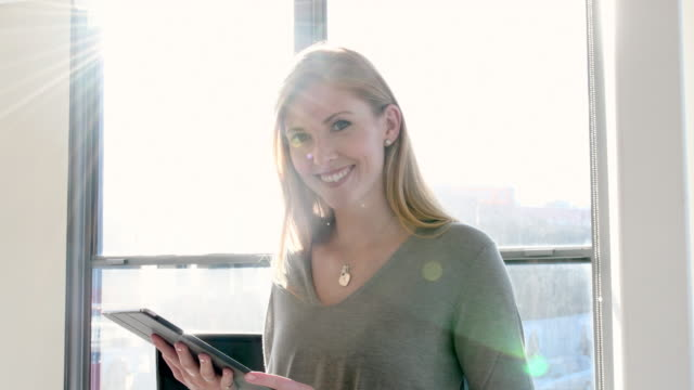 Businesswoman using tablet PC in brightly office video
