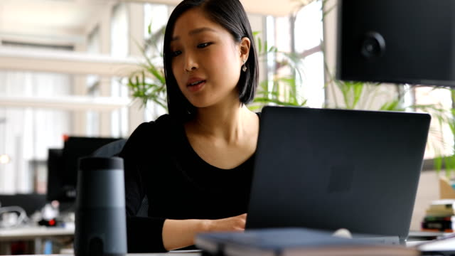 businesswoman using virtual assistant at desk - assistente virtuale video stock e b–roll