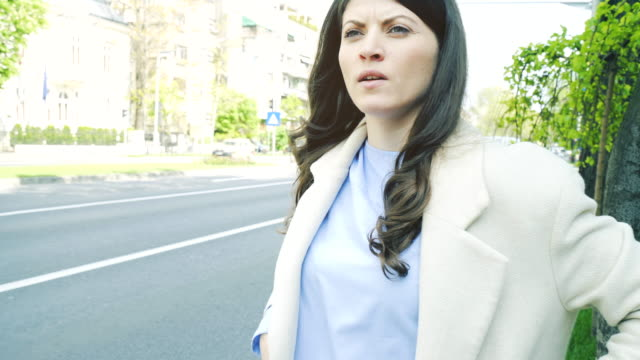 Businesswoman waiting in the street for an Uber or a taxi car. video