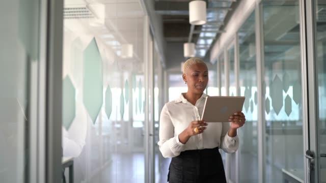 affärskvinna går och gör ett videosamtal på digital surfplatta på jobbet - affärskvinna bildbanksvideor och videomaterial från bakom kulisserna