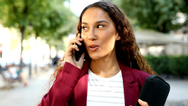 businesswoman walking and talking on phone - ear talking video stock e b–roll