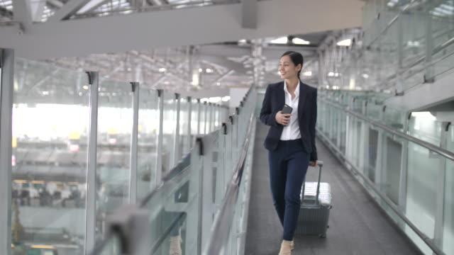 stockvideo's en b-roll-footage met zakenvrouw wandel- en met behulp van slimme telefoon op luchthaven, zakelijke reizen - business woman phone