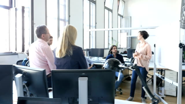 Businesswoman walking during meeting at office Colleagues looking at businesswoman walking during meeting at workplace. Businesswoman standing amidst whiteboard and coworkers at creative office. They are wearing smart casuals. medium group of people stock videos & royalty-free footage