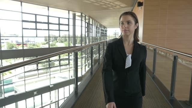 geschäftsfrau zu fuß in büro-gebäude zeitlupe - weibliche führungskraft stock-videos und b-roll-filmmaterial