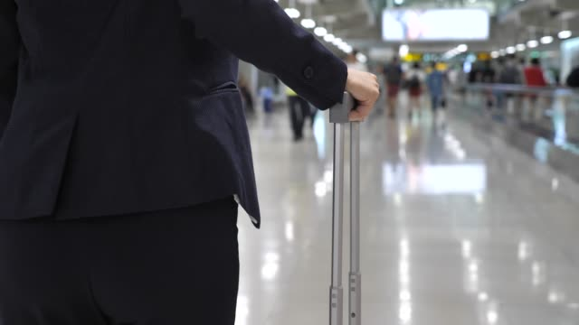 Businesswoman walking on airport and roll suitcase