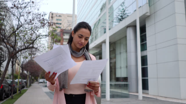 Businesswoman walking outside while checking some office paperwork Businesswoman walking outside while checking some office paperwork - Lifestyles mid adult stock videos & royalty-free footage