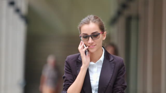 Businesswoman walking towards the camera and speaking phone video