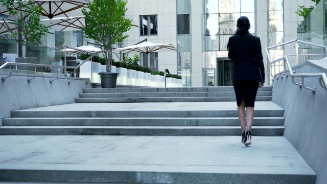 Businesswoman walking up the stairs to building, backside view, career ladder video