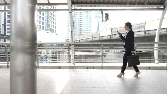 市内でスマートフォンで歩くビジネスウーマン、通勤 - women leaders点の映像素材/bロール
