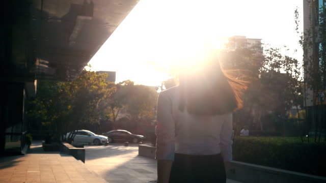 Businesswoman walking with sunlight video