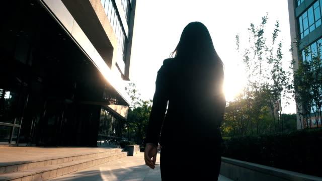 geschäftsfrau, die zu fuß mit sonnenlicht - rücken stock-videos und b-roll-filmmaterial