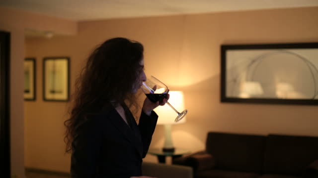 Businesswoman watching TV and enjoying a glass of wine video