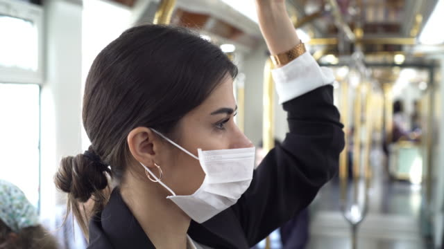 Businesswoman wearing a mask while traveling Businesswoman wearing a mask while traveling. covid mask stock videos & royalty-free footage