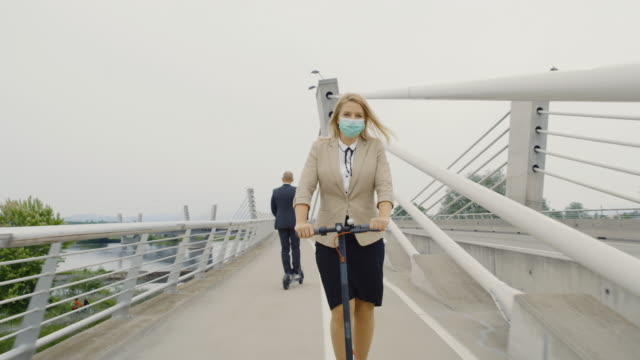 SLO MO Businesswoman wearing a surgical mask while riding an electric scooter to work Slow motion shot of a businesswoman wearing surgical mask while riding electric scooters on a bridge to work. Man in formalwear also riding an electric scooter in opposite direction. Shoot in 8K resolution. alternative fuel vehicle videos stock videos & royalty-free footage