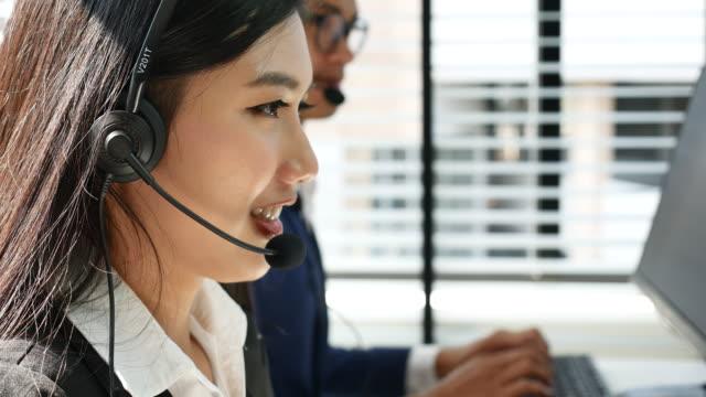 Businesswoman wearing headset using computer video