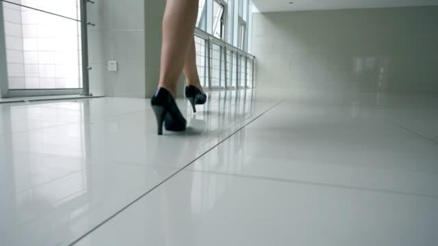 vídeos de stock, filmes e b-roll de empresária de saltos andando no corredor do escritório - salto alto