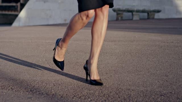 stockvideo's en b-roll-footage met zakenvrouw dragen van hakken lopen in de stad. close-up op de benen - street style