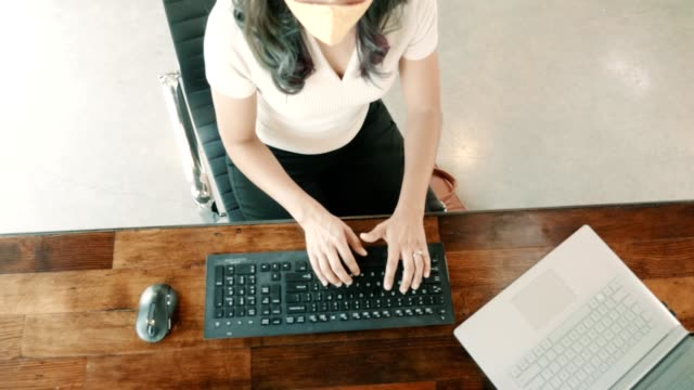 Businesswoman wears protective face mask while working in office