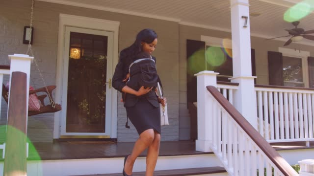 businesswoman with baby son leaving house for work - dolly shot video stock e b–roll